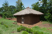 Home made from mud with a thatched roof, with a neat garden in rural Kenya.