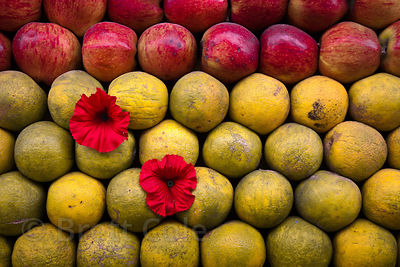 Flowers adorn oranges and apples for sale on a street cart in Ajmer, Rajasthan, India