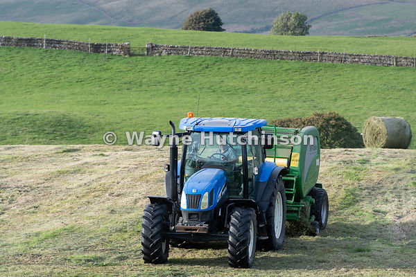 Making big bales of silage n an upland meadow with a New Holland TS135 Tractor and McHale F5500 baler. Wensleydale, UK.