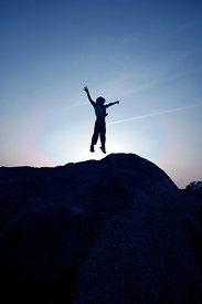 Boy silhouette jumping on rock with arms up in the air