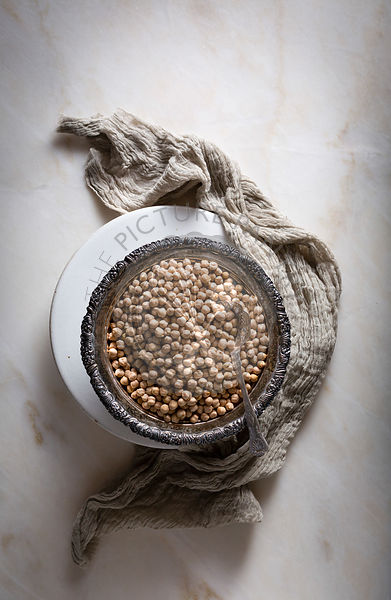 Raw chickpeas /garbanzo beans in a silver bowl on top view