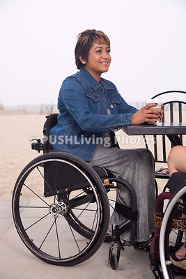 Two women in wheelchairs at a beachside cafe