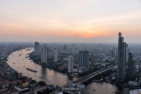 Looking at the Chao Phraya River from the Sky Bar at State Building in Bangkok, Thailand at sunset.