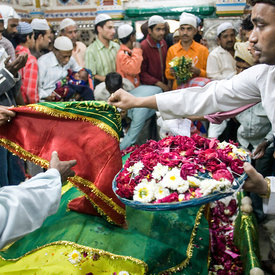 Worshippers (both Hindu and Muslim) pray and make offerings over the tomb of Hazrat Nizamuddin Awlia, a sufi saint who died in AD 1325