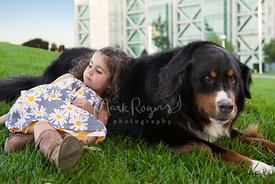 Girl leaning against large dog on the grass