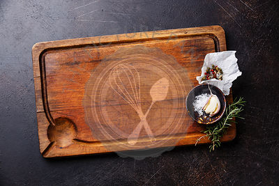 Wooden cutting board background with seasoning on dark background copy space