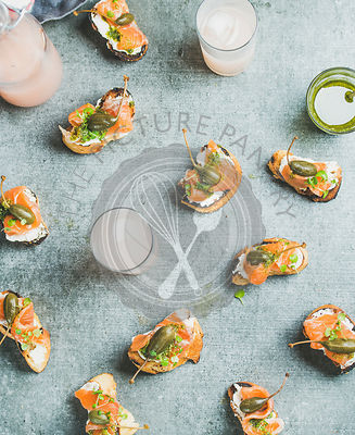Crostini with smoked salmon, pesto sauce, watercress and capers and pink grapefruit cocktails over grey background, top view, flay-lay