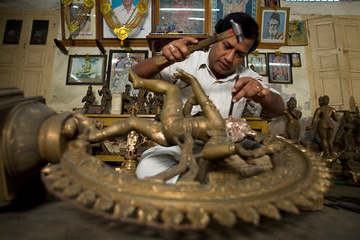 India - Swamimalai - Master craftsman Radhakhrishna Staphaty, works on the final touches to a statue of the dancing Nataraja at dawn