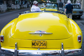The back  of an antique yellow car in Havana, Cuba.