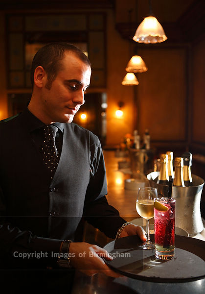 Bar tender carrying a tray of drinks from the bar, Hotel du Vin, Birmingham