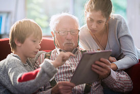 His grandchildren teach their grandfather how to use a tablet.