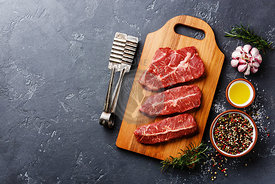 Raw fresh meat Top Blade steaks on wood cutting board on dark background copy space