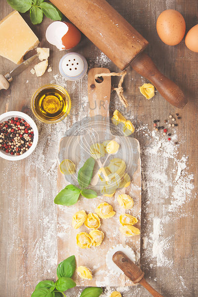 raw italian pasta tortellini with ingredients on wooden board. Top view