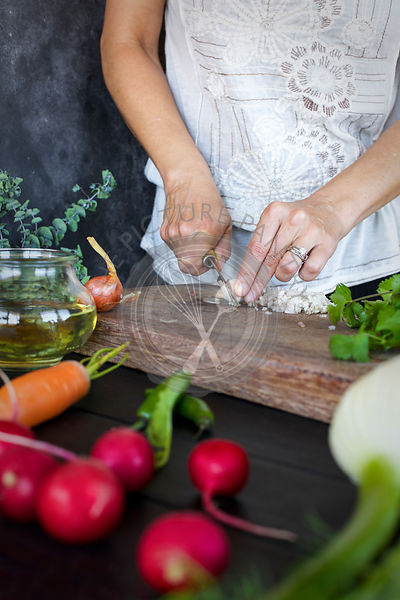 Women preping for Quick Pickled Veggies. Photographed on a black wooded background.
