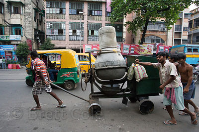 Laborers haul a cement mixer down a road in Bhawanipur, Kolkata, India