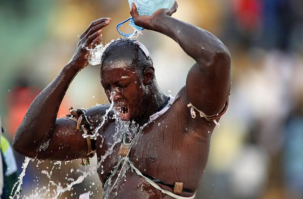 Combat between Issa Pouye and  Zoss at Demba Diop Stadium in Dakar. Issa Pouye mystical preparation before the fight. The wrestler splashes of various liquids prepared by their marabouts.
