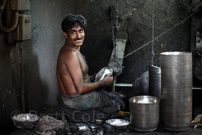 A man works at a metal fabrication shop without any health precautions, Beniatola, Kolkata, India. Respiratory disease is a major problem in India.