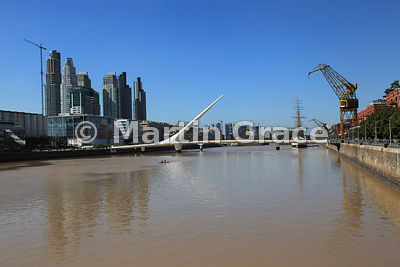 Puente de la Mujer (Woman Bridge) in Puerto Madero docklands regeneration in Buenos Aires, Argentina, with high rise buildings and restored cranes