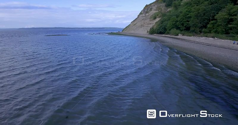 Backing shot over small waves lapping a sandy and forested beach with bluffs