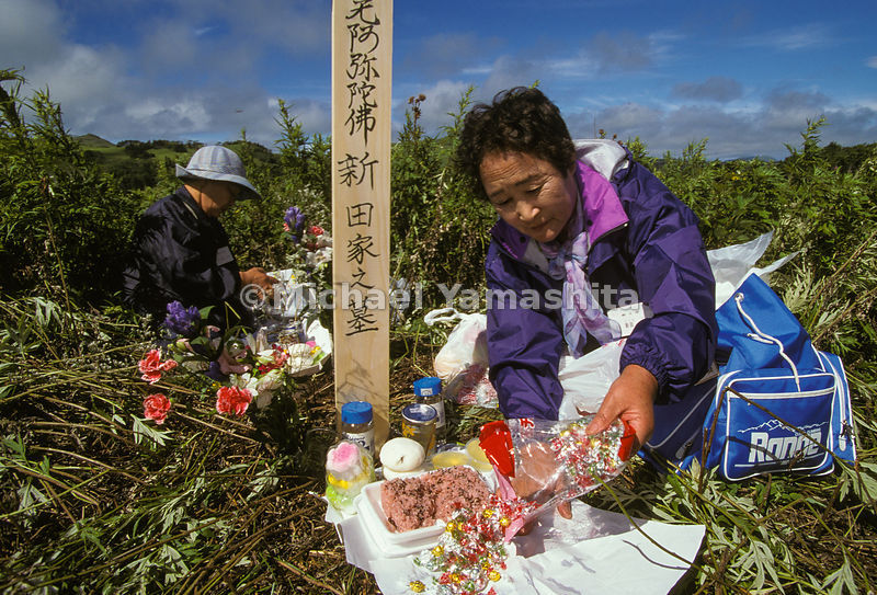 Japanese visiting graves...ancestors, candle, flowers, grave, japan, Kuril Islands, Kurils, mourning, National Geographic, offering, overgrown, People, plot, red rice, respect, sake, Shikotan, woman