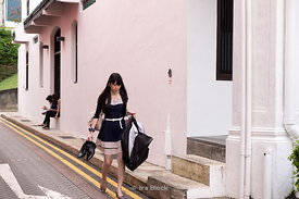 A woman holding a pair of men's shoes and clothes on a street in Emerald Hill, Singapore.