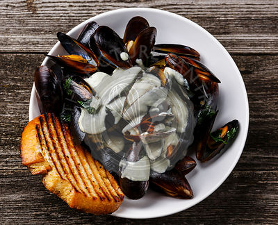 Mussels Clams in Blue cheese sauce and toasted bread on wooden background