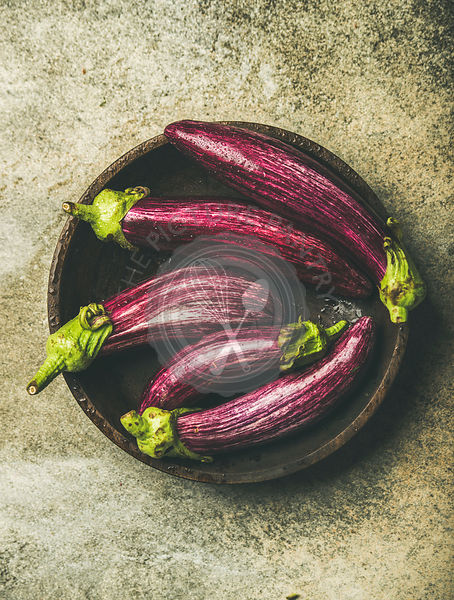 Flat-lay of fresh raw Fall harvest purple eggplants or aubergines in wooden bowl