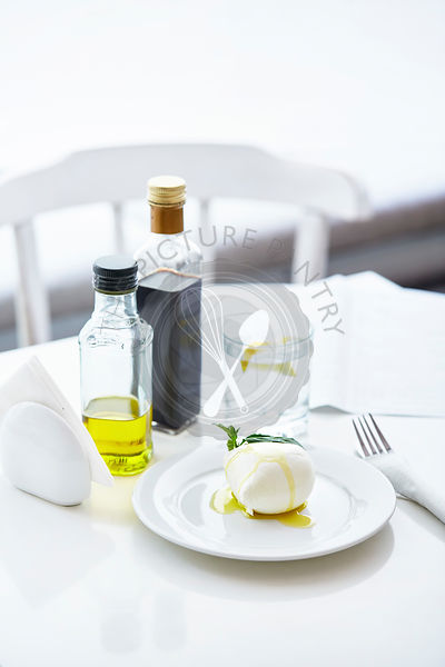Fresh buffalo mozzarella ball with olive oil, basil and balsamic on white table