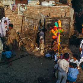 A child sells balloons while passersby chat in the lanes of Kathputli Colony