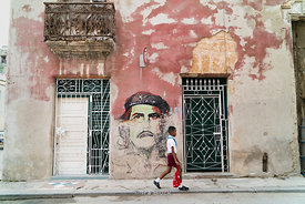 A school boy walks past an altered mural of Che Guevara in the Old City, Havana, Cuba