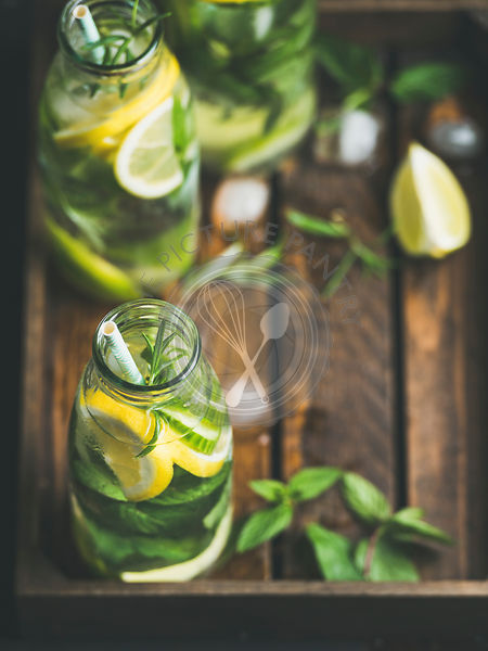 Citrus fruit and herbs infused sassi water for detox, healthy eating, dieting in glass bottles in wooden tray, copy space