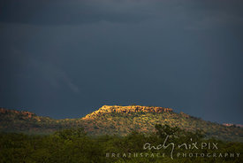 Sunlight on a rock outcrop against black sky