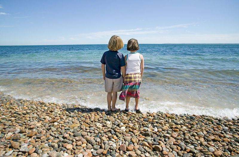 boy and girl looking at water on beach
