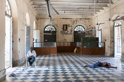 A building worker asleep on a break inside the derelict Hotel du Ville that has been saved by INTACH (Indian National Trust for Art and Cultural Heritage). Pondicherry, India