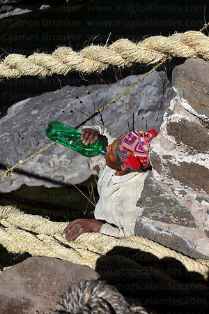 Man has a drink of chicha (maize beer) after tying rope to one of the main foundation ropes (so it can be tensioned), Q'eswachaka , Canas province , Peru
