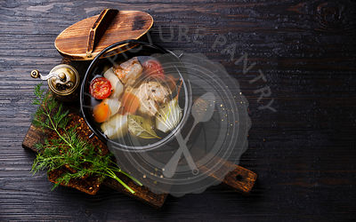Fish soup with salmon, potato and carrot in black iron pot on black burned wooden background copy space