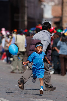 A boy watches a parade in Cusco, Peru
