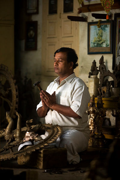 India - Swamimalai - Master craftsman Radhakhrishna Stpathy, prays and offers a devotion at dawn before carving the eyes into a statue of the dancing Nataraja
