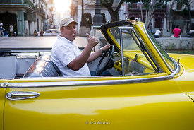 A driver in an antique yellow car in Havana, Cuba.