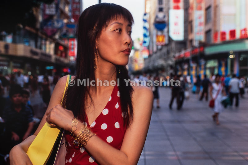 A young lady walks through Nan Jing East Road is the most popular shopping street in Shanghai, China.