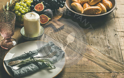 Plate with napkin, fork, spoon, glass, candle, grapes and figs on board, buns, olive tree branch over wooden background, copy space