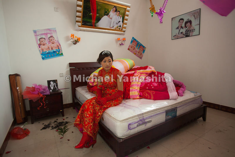 Canal villages reflect the tug of China's past and its present. Birde-to-be Wei Li, 23, wears a traditional red gown for the ceremony in the fishing village of Xiaxinzhuang, on Weishan Lake. Photos on the wall of what will be the newlywed's bedroom, taken weeks earlier, show her in Western-style garb.