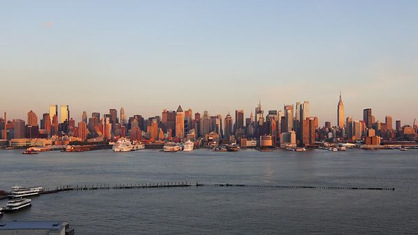 Medium Shot: Cruise Ships Leaving Port As Manhattan Switches On For The Night