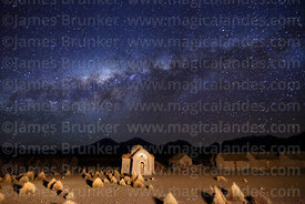 Thatched adobe houses, ruined Rosario chapel and Milky Way Galactic Centre, Estancia Huincurata, Sajama National Park, Bolivia