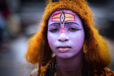 A boy dressed as Shiva to make money from India photographers taking his photos during Mahalaya observance, Babughat, Kolkata, India