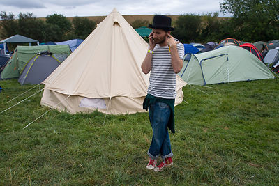 UK - Standon - A man makes a telephone call on his cellular mobile telephone next to a field of tents at the Standon Calling Festival