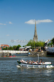 Tourist boat on floating harbour, with the spire of St Mary Redcliffe in distance,  bristol, england.