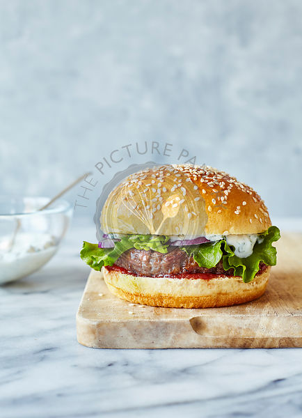 Lamb burger in brioche bun with mint yoghurt, served on a wooden board