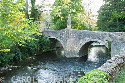Bridge over the River Frome, 1400, with 18th century statue of Britannia installed by Peto. Iford Manor, Bradford-on-Avon, Wiltshire
