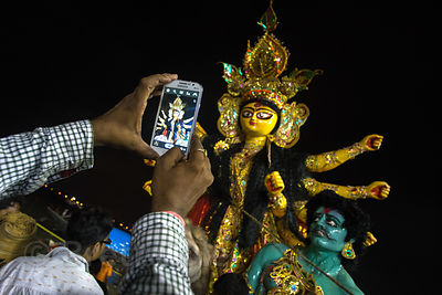 A man photographs a Durga Puja idol during immersion in the Hooghly River, Babughat, Kolkata, India